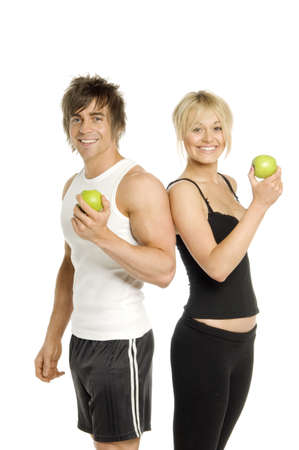 Muskul�ser Mann und h�bsche blonde Frau stand mit gr�nen �pfeln auf einem wei�en Hintergrund