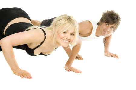 Pretty blonde woman and muscular man doing push up exercises isolated on a white background photo