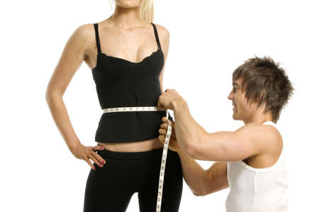 Athletic man measuring woman in gym wear isolated on a white background photo