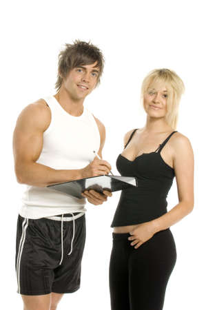 Athletic man and woman in gym wear filling in a form isolated on a white background