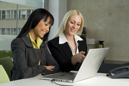 Two beautiful business colleagues working on a laptop together photo