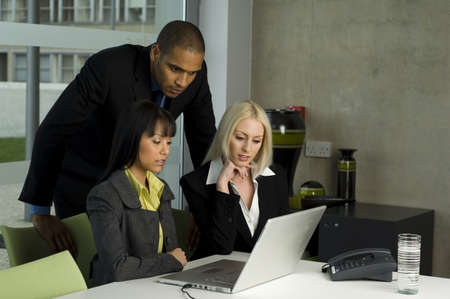 Three colleagues working together at a laptop photo