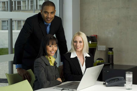 Three work colleagues working together on a laptop photo