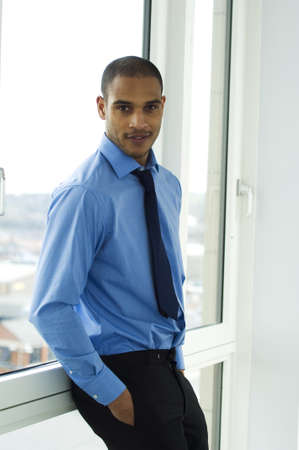 Business man leaning against a window wearing a blue shirt and tie photo
