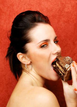 gula: Siete pecados - glotoner�a - Una hermosa mujer de comer pastel de chocolate en un fondo rojo, que representa la gula