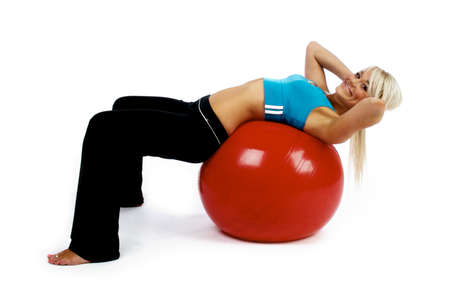 Young blonde woman working out on a red fitness ball isolated on a white background Stock Photo