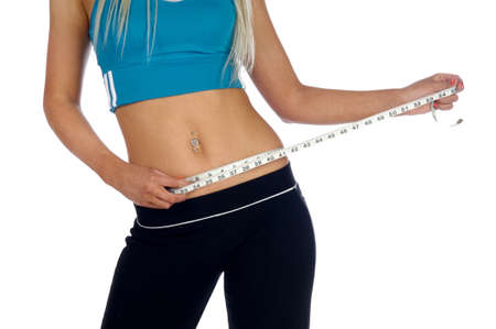 Young woman measuring her waist with a tape measure isolated on a white background photo