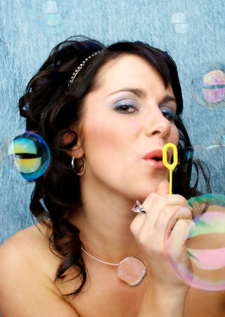 slovenly: Seven Sins - Sloth - A beautiful woman wasting time blowing bubbles on a blue background Stock Photo