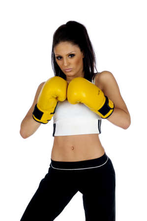 Young brunete woman wearing yellow boxing gloves isolated on a white background photo