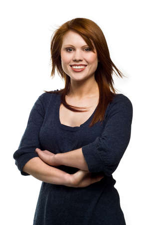 Beautiful young red haired woman smiling wearing a navy blue sweater, isolated on a white background Standard-Bild