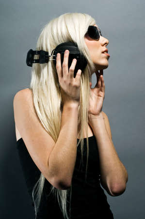 Beautiful young blonde woman with headphones on a grey background Stock Photo