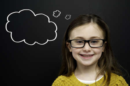Smart young girl wearing a yellow jumper and glasses stood infront of a blackboard with a drawn on chalk thought bubble Standard-Bild