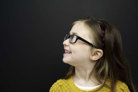 Smart young girl wearing a yellow jumper and glasses stood infront of a blackboard