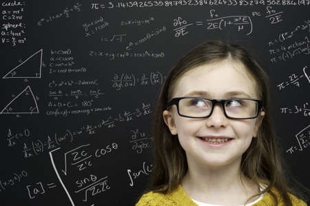 Smart young girl wearing a yellow jumper and glasses stood infront of a blackboard with mathematical equations written in chalk