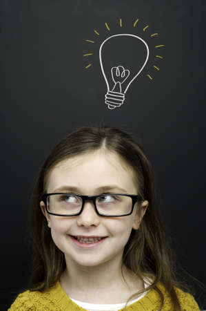 Smart young girl wearing a yellow jumper and glasses stood infront of a blackboard with a drawn on chalk light bulb photo