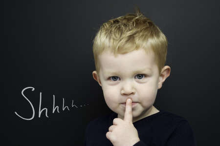 shush: Smart young boy wearing a navy blue jumper stood infront of a blackboard with his finger over his lips being quiet