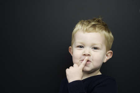 Smart young boy wearing a navy blue jumper with his finger over his mouth being quiet stood in front of a blackboard