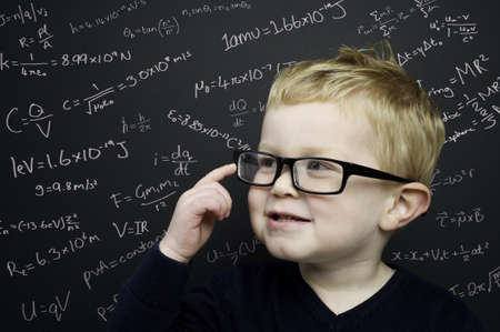 Smart young boy wearing a navy blue jumper and glasses stood infront of a blackboard with scientific formulas and equations written in chalk Standard-Bild
