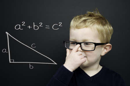 Smart young boy wearing a navy blue jumper and glasses stood infront of a blackboard with the Pythagoras rule explained drawn in chalk Standard-Bild