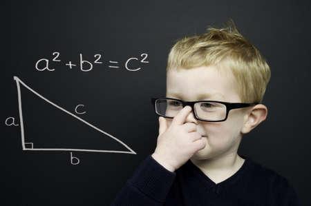 Smart Junge tr�gt einen dunkelblauen Pullover und Gl�ser standen infront einer Tafel mit dem Pythagoras Regel erl�utert Kreide gezeichnet Lizenzfreie Bilder