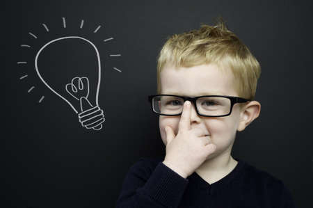 Smart young boy wearing a navy blue jumper and glasses stood infront of a blackboard with a drawn on chalk light bulb Standard-Bild