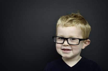 Smart boy wearing black rimmed glasses stood smiling infront of a blackboard young Stock Photo