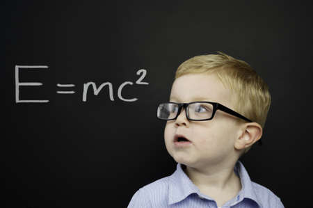 Smart young boy wearing a blue shirt and glasses stood in front of a blackboard with E=mc2 written in chalk