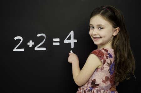 Intelligente junge M�dchen tr�gt ein rotes Kleid schriftlich Mathematik Summen auf einer Tafel Lizenzfreie Bilder