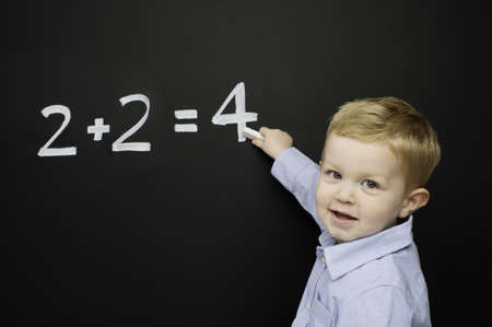 Smart young boy wearing a blue striped shirt stood writing a math sum on a blackboard