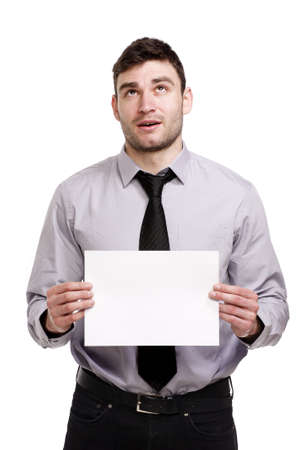 Handsome business man isolated on a white background looking up thinking while holding a blank sign Stock Photo - 18495228