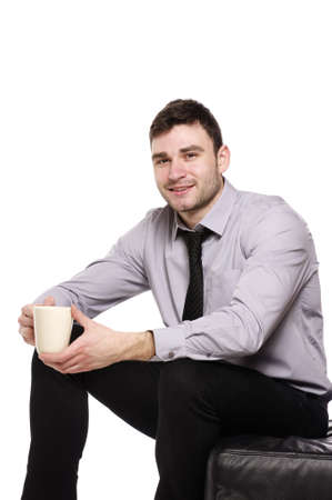 Handsome business man sat isolated on a white background holding a cup of coffee Stock Photo - 18495216