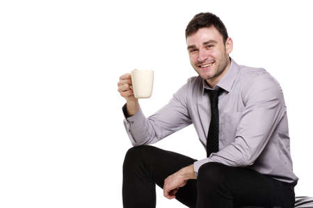 Business man sat isolated on a white background smiling at the camera holding a cup of coffee Stock Photo - 18495195