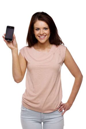 casually dressed: Beautiful brunette woman casually dressed isolated on a white background holding up a mobile phone Stock Photo