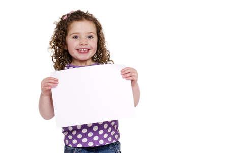 ni�os sosteniendo un cartel: Ni�a con un cartel en blanco liso aislado en un fondo blanco, sonriendo a la c�mara