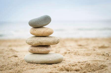 piedras zen: Cinco piedras en equilibrio encima de otro en una playa de arena