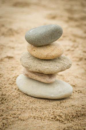 F�nf Steine ??�bereinander auf einem Sandstrand ausgeglichen Lizenzfreie Bilder