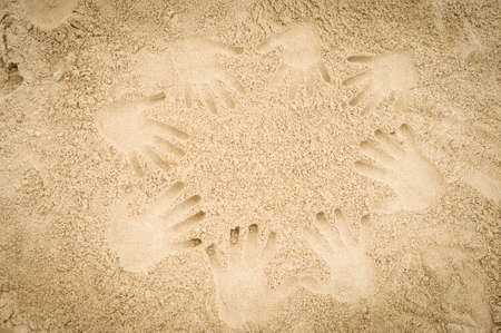 Hand prints on a sand beach in a circular shape photo