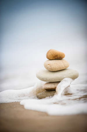 Five stones balanced on top of eachother as the tide comes in and wraps around them