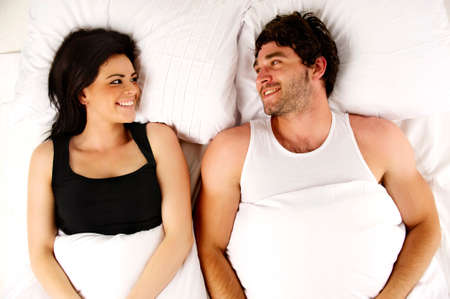 next to each other: Beautiful couple laid in a white bed next to each other smiling
