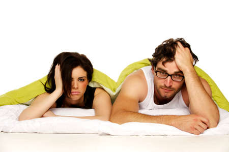 upset woman: Attractive couple laid in bed under a green duvet looking tired and miserable in the morning Stock Photo