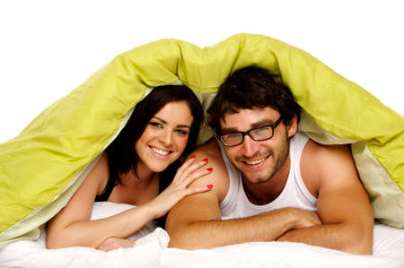 Attractive couple laid in bed together in the morning under a green duvet smiling at the camera