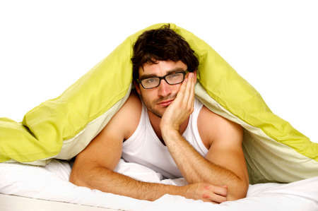 Attractive man laid in bed under a green duvet looking tired and fed up in the morning wearing glasses