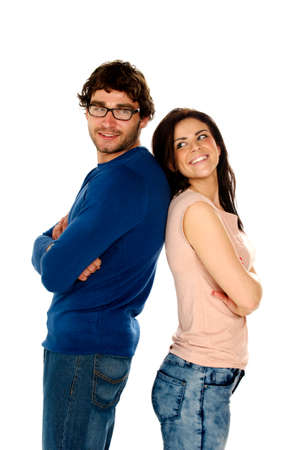 Cute dark haired couple stood back to back smiling at the camera isolated on a white background photo