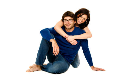 Cute dark haired couple cuddling smiling at the camera isolated on a white background photo