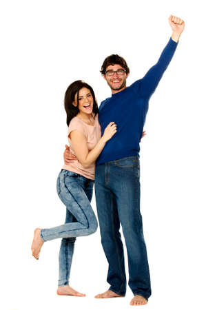 Attractive dark haired couple stood cheering and celebrating isolated on a white background photo