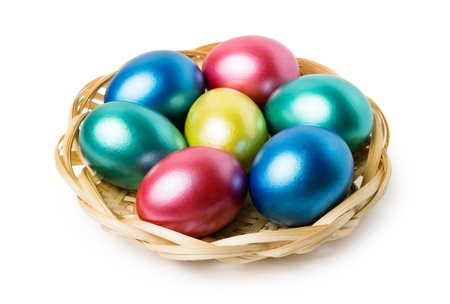 Multi-colored Easter eggs in basket isolated on white background photo