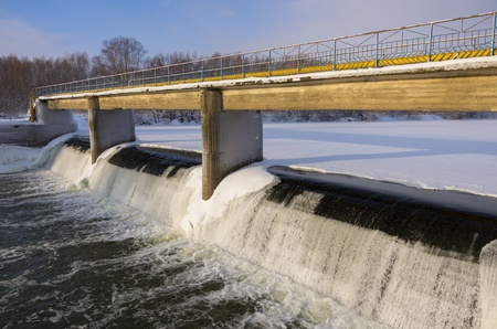 Dam through small river in winter photo