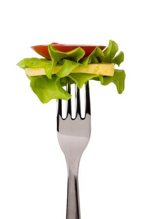 cubiertos de plata: Rebanada de tomate, lechuga y queso en tenedor aisladas sobre fondo blanco