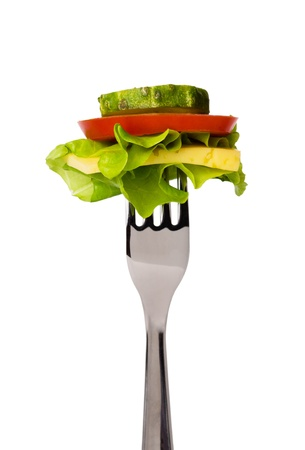 Tomato slice, lettuce, cucumber and cheese on fork isolated on white background