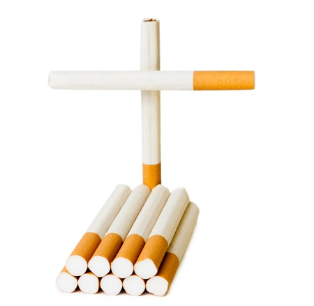 Grave headstone and cross of cigarettes isolated on white background photo